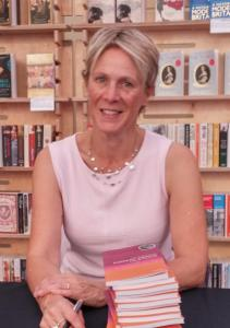 Woman smiles at the camera. She is in a pink top and wearing a necklace. In front of her is a pile of books, and in one hand is a pen.