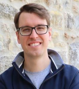 A man in glasses faces the viewer and smiles. He is wearing a navy blue jumper and pale blue t shirt.