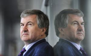 A man stares into the distance. He is wearing a blue suit with white shirt. There is a mirror image of him reflected in the glass wall he leans against