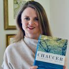 Smiling woman faces camera. She is holding a copy of her book 'Chaucer; A European Life', is against a white background, and is wearing a cream jumper